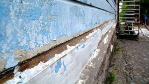 En husvägg som behöver målas om samt en byggställning.
