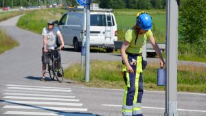 En kvinna reparerar trafikljusen vid ett övergångsställe.