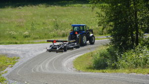 Traktor plattar väg i Norrbacka, Kimito.