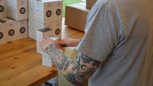 En person i grå t-skjorta viker kaffepaket.