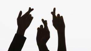 Bild på tre händer med korsade fingrar.