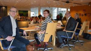 Fyra talar med publik i bakgrunden.