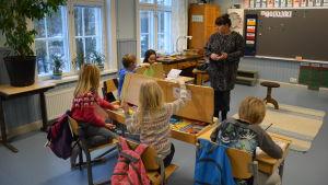 Lärare står framför en liten grupp elever i ett klassrum.