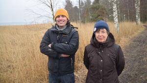 En glad man i gul mössa och en kvinna i blå mössa pÅ Lilludden i Ingå. De heter Benjamin Lundin och Elisabeth Liljeqvist.