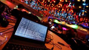 En bärbar dator med kod i skärmen ligger på ett bord.
