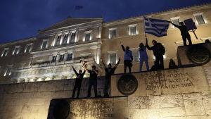 Människor viftar med den grekiska flaggan utanför parlamentsbyggnaden.