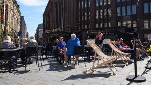 Folk sitter och njuter av värmen på en uteservering utanför Stockmanns varuhus.