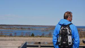Turist blickar ut över Kvarkens världsnaturarv från utkikstornet saltkaret i Svedjehamn i Björkö.