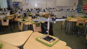 Stolar är upp och ner på pulpeter i ett klassrum.
