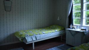 Sovrummet på Lillholmen. Sängen är bäddad med Muminlakan.
