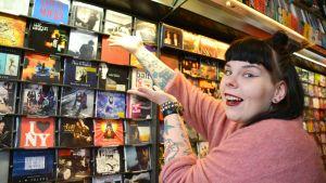 Maria Ahonen i en skivbutik, pekar mot en skiva av Antti Tuisku.