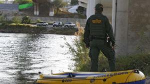 En gränskontrollant vid floden Rio Grande - i förgrunden en gummibåt som migranter tros ha använt för att ta sig över gränsen.