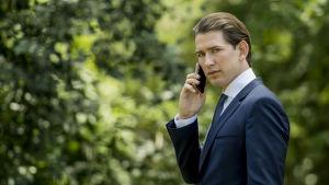 Österrikes utrikesminister Sebastian Kurz talar i telefon.