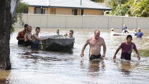 Invånarna i Mount Warren Park i Queensland deltog i räddningsarbetet medan barnen lekte på surfbrädor