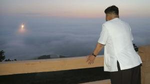 Odaterad bild där Nordkorea avfyrar en missil med ledaren Kim Jong Un som åskådare.
