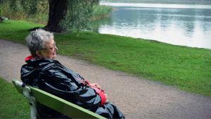 Författaren Ann-Mari Lindberg sitter på en bänk och tittar ut mot havsviken intill Lappvikens sjukhus.