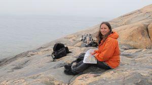 Luontotoimittaja Minna Pyykkö istuu kalliolla.