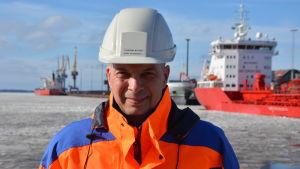 Torbjörn Witting står på kajen i Karleby hamn, bakom syns flera fartyg. Vinter och is i hamnen