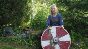 Emelie Lytz sitter på en sten i klädd vikingakläder med ett svärd och ett sköld framför sig.