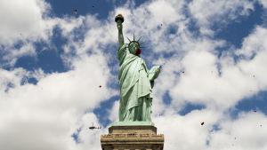 Frihetsgudinnan mot en blå himmel med vita moln.
