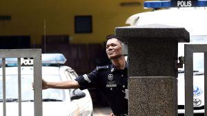 Polis står vakt utanför sjukhuset där mördade Kim Jong-nams kropp förvaras.
