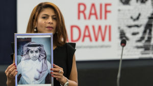 Ensaf Haidar, wife of jailed Saudi blogger Raif Badawi, holds a picture of her husband in the European Parliament in Strasbourg