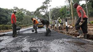 Kenyanska vägarbetare asfalterar en väg inför president Barack Obamas besök i landet i juli 2015.