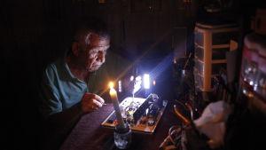 En man reparerar elektrisk apparatur i skenet av ett stearinljus i San Christobal, Venezuela 26.4.2016