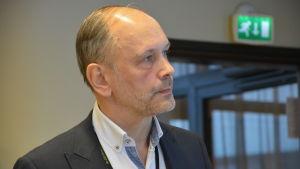 Direktör Kjell Henrichson står på möte i vit kavaj och vit skjorta.