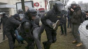 Säkerhetspolisen bär en demonstrant i Minsk. Till höger står en journalist och fotograferar händelsen.