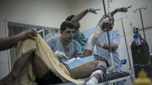 Läkare opererar skadad man efter bombningar i Aden.