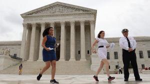 Praktikanter springer för att leverera dokument till reportrar utanför Högsta domstolens byggnad i Washington DC.