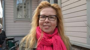 Väljaren Pauliina Vanhala hoppas på aktivt valdeltagande. Kvinna i övre medelåldern, ljusbrunt hår, grannröd halsduk ska rösta i Åbo.