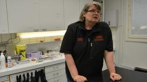 veterinär tiina anttila står bakom ett skötbord med veterinärredskap i bakgrunden