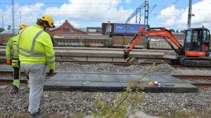 Två byggnadsarbetare står med ryggen vända vid ett brobygge över järnvägsspår.