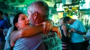 nainen ja mies halaavat baarissa