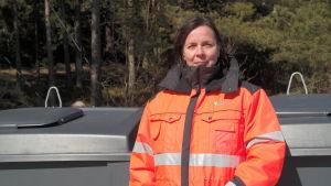 Cati Huhta står vid ett avfallskärl i Kirjais i Nagu