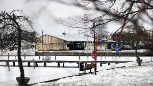 En vy över en hamn i vinterskrud. I bakgrunden syns en gul gammal magasinbyggnad.