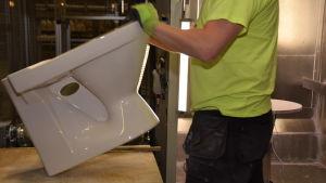 En arbetare på Ido badrums fabrik i Ekenäs granskar med sina händer att wc-stolen är hel.