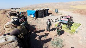 Kurdiska peshmergasoldater utanför byn Basheqa, i väntan på att rycka framåt mot Mosul.