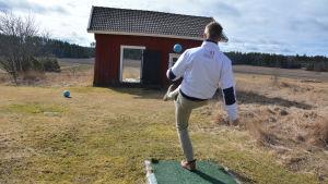 Ung man försöker sparka en boll genom ett litet hus.