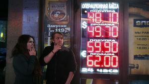 Ryssari Moskva  röker vid en informationstavla som visar valutakurserna 28.11.2014.