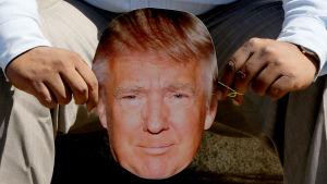En demonstrant håller upp en Trump-mask vid en demonstration i Indien
