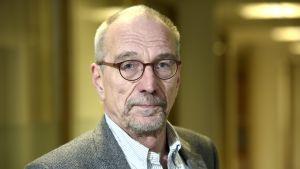 Porträtt av Nils Torvalds i grå kostym och runda bruna glasögon.