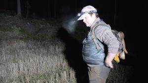 Jägare med pannlampa och ryggsäck i mörk skog.