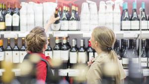 En försäljare lyfter ner en rödvinsflaska åt en kund.