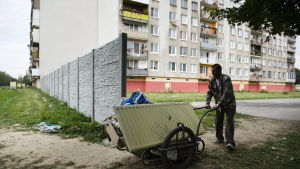 En romsk man knuffar sin kärra förbi den mur som lokalbefolkningen låtit bygga runt en romsk bosättning i Slovakien 2010.
