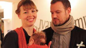 Ett par håller sin bebis på en namngivningsfest