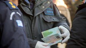 Grekisk polis granskar flyktingars id-handlingar.