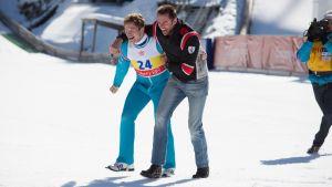 Taron Egerton och Hugh Jackman lämnar jublande hoppbacken med en kameraman i hälarna.
